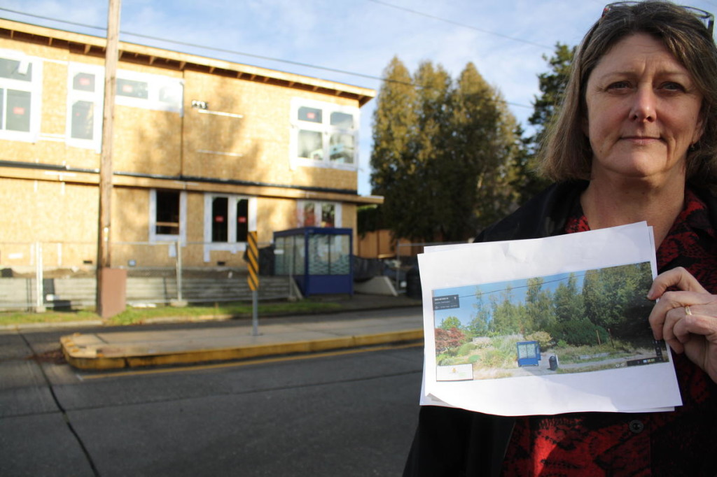Cass Turnbull stands before a former substation site. She holds a Google Street View image showing the landscaping recently removed to make way for townhomes.
